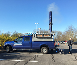 Man standing behind a blue truck in a parking lot as smoke rises from the stack.
